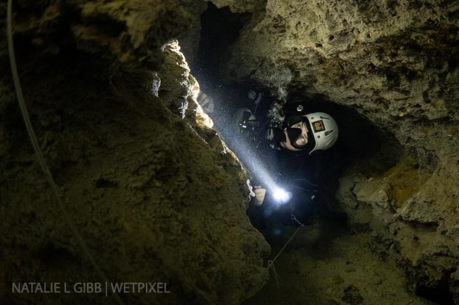 Bre Kramer slides through a tight restriction at Cenote Caterpillar.