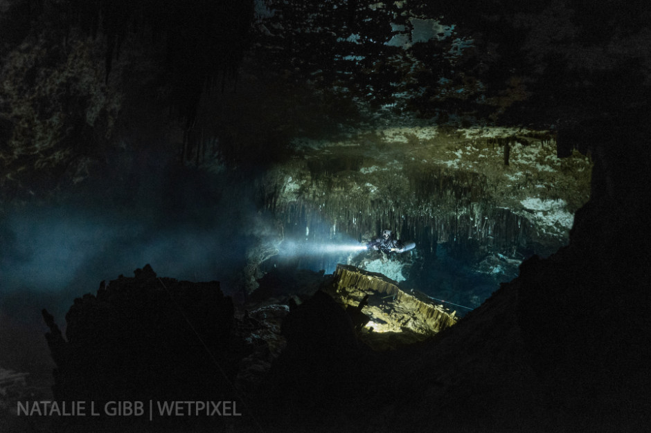 Glenn Farquhar's strong primary light punches into the darkness, illuminating sediment in the water and giving a sense of depth to this photo from Cenote Minotauro.