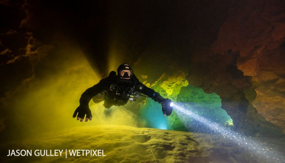 Cave diver Jaime De La Puerta Salazar fins through a layer of green-tinged groundwater sandwiched between tannic river water on the ceiling and the silty floor of Peacock Springs.