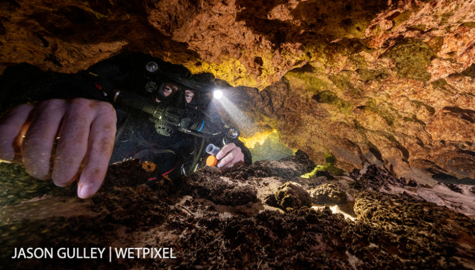 Cave diver and science volunteer Tim Senkovitch collects mineral deposit samples for a group of non-cave diving scientists who are waiting for him on the surface.