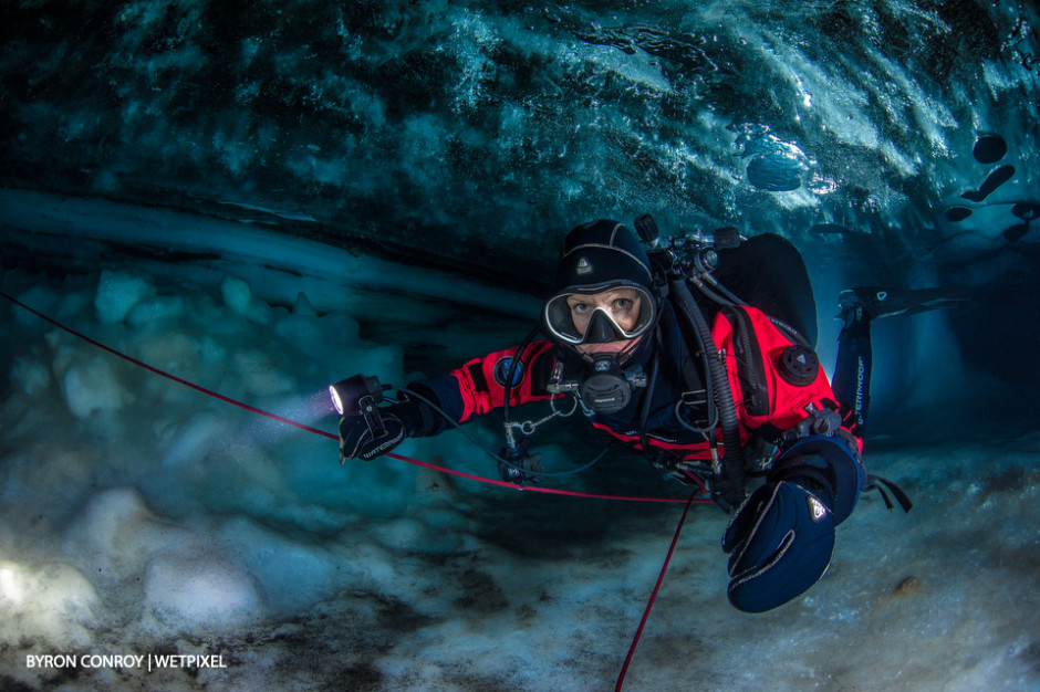 A model poses in an ice cave.