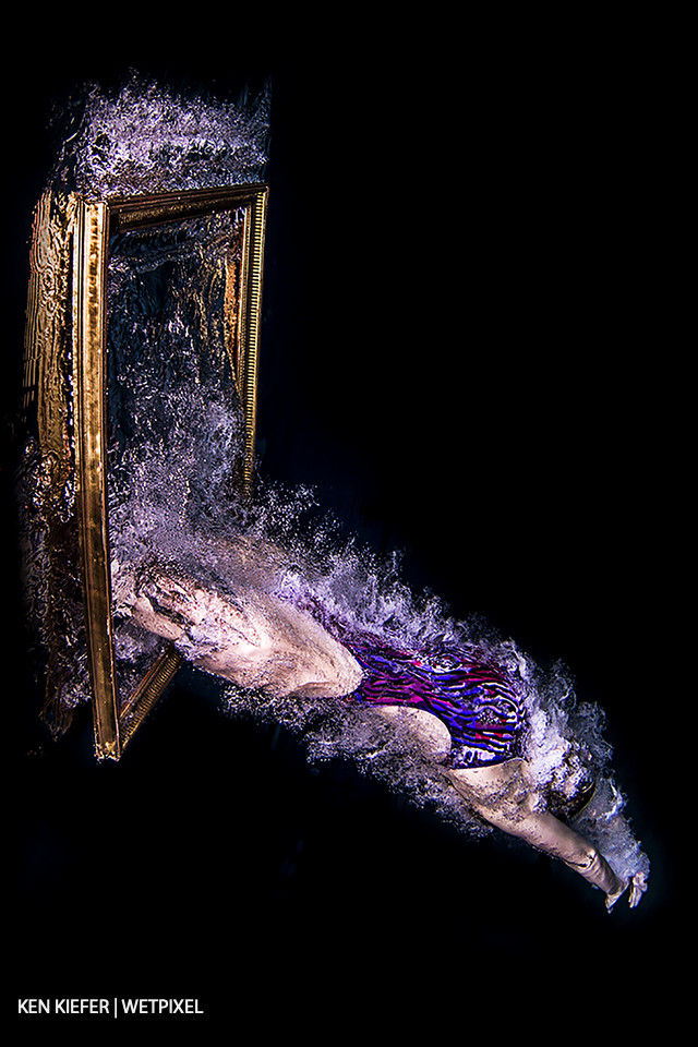Diving through a frame on the surface of the water with a black backdrop.