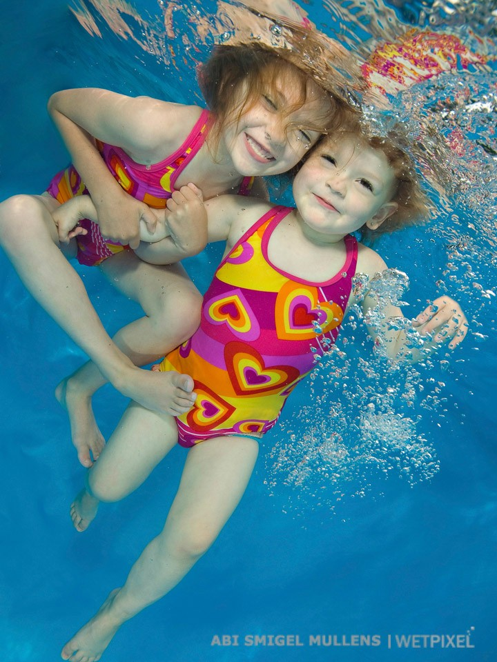 Adorable sisters heart to heart underwater.