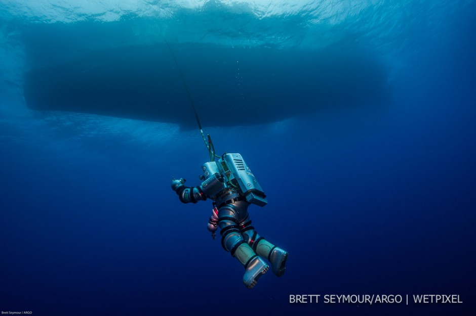 The Exosuit, a single person one atmosphere diving hard suit is suspended from the Hellenic Navy vessel HN THETIS.