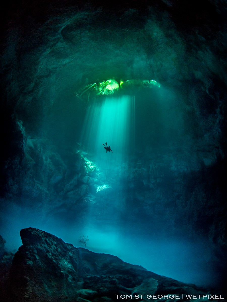 A solo diver ascending in the sunbeams at the majestic Cenote El Pit